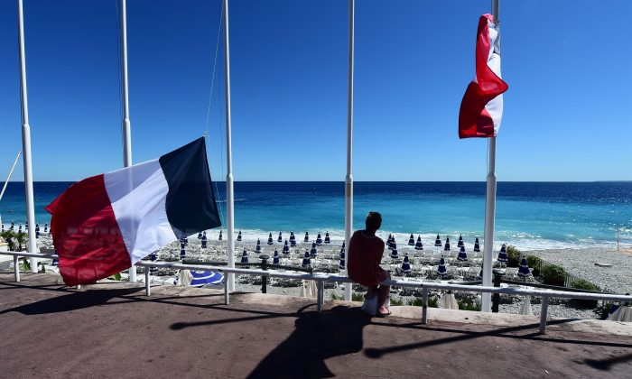 A woman sits under French flags lowered at half-mast in Nice on July 15, 2016, following the deadly Bastille Day attacks. (GIUSEPPE CACACE/AFP/Getty Images)