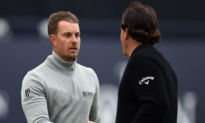 US golfer Phil Mickelson (R) and Sweden's Henrik Stenson shakes hands on the 18th green after their third rounds on day three of the 2016 British Open Golf Championship at Royal Troon in Scotland on July 16, 2016. Sweden's Henrik Stenson leads the British Open by a single shot from Phil Mickelson after the third round following his superb 68 on Saturday. Stenson, bidding to win his first major at the age of 40, had five birdies and two bogeys in his three-under-par round to move to 12-under for the championship.  / AFP / GLYN KIRK / RESTRICTED TO EDITORIAL USE        (Photo credit should read GLYN KIRK/AFP/Getty Images)