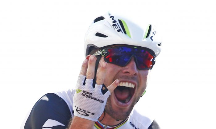 Dimension Data's Mark Cavendish flashes four fingers for his fourth victory in this year's Tour de France as he crosses the finish line to win Stage 14, 208.5 kilometers (129.2 miles) from Montelimar to Villars-les-Dombes, France, Saturday, July 16, 2016. (AP Photo/Peter Dejong)