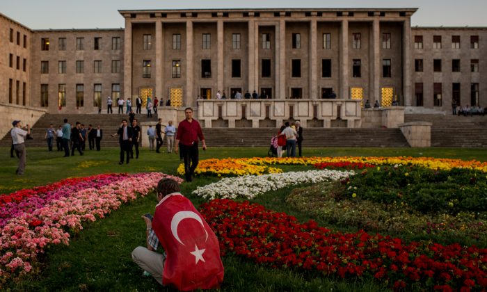 A man sits in front of Parliament House after listening to official speeches during a rally in reaction to the attempted military coup in Ankara, Turkey, on July 16, 2016. (Chris McGrath/Getty Images)