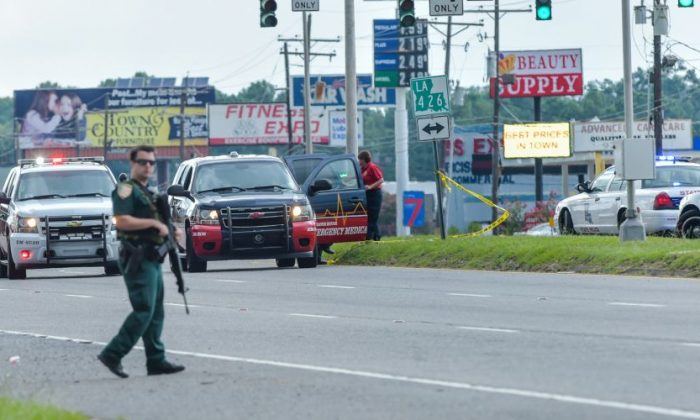 Baton Rouge police respond to active shooter near Hammond Aire Shopping Center in Baton Rouge, Sunday, July, 17, 2016. Multiple law enforcement officers were killed and wounded Sunday morning in a shooting near a gas station in Baton Rouge, less than two weeks after a black man was shot and killed by police here, sparking nightly protests across the city. (Scott Clause/The Daily Advertiser via AP)