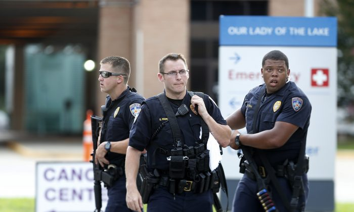 Police guard the emergency room entrance of Our Lady Of The Lake Medical Center, where wounded officers were brought, in Baton Rouge, La., Sunday, July 17, 2016. (AP Photo/Gerald Herbert)