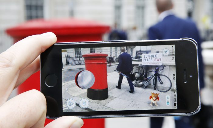 A Spearow, a Pokemon character appears on a London street while a man plays Pokemon Go on July 15, 2016. (Olivia Harris/Getty Images)