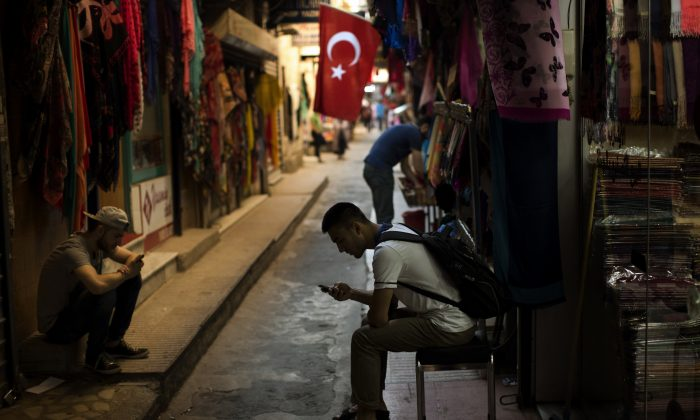 Sellers wait for customers as they look at their phones in central Istanbul, Monday, July 18, 2016. Warplanes patrolled Turkey's skies days after a failed coup, officials said Monday, in a sign that authorities feared that the threat against the government was not yet over. (AP Photo/Emilio Morenatti)