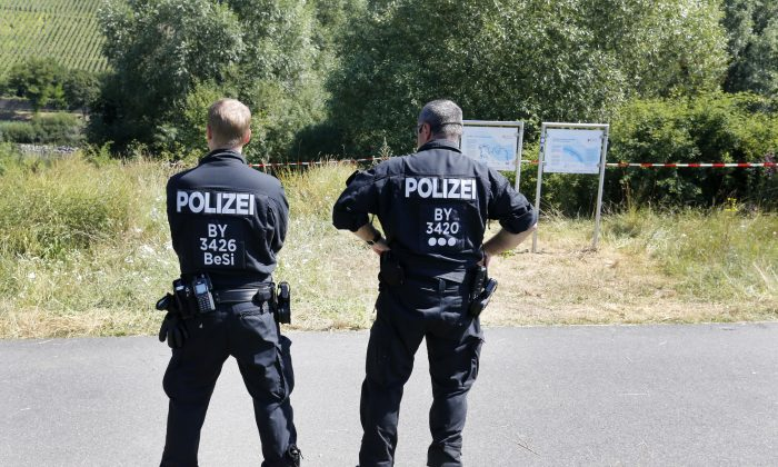 Police officers stand at the crime scene near the river Main, background, where a 17-year-old man from Afghanistan was shot the night before, in Wuerzburg, Germany, Tuesday, July 19, 2016. On Monday evening, the man wielding an axe and knife attacked travelers on a regional train near Wuerzburg.  Four people were seriously injured. He was shot and killed by police as he fled. (AP Photo/Michael Probst)
