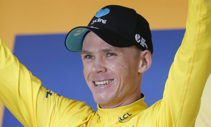 Sky's Chris Froome, wearing the overall leader's yellow jersey, celebrates on the podium after Stage Nine of the Tour de France, July 10, 2016. (AP Photo/Christophe Ena)