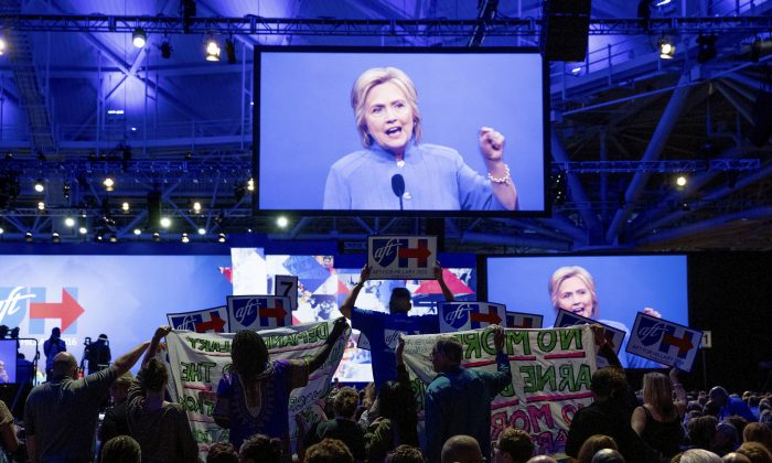 Clinton supporters try to block signs held by protesters as they disrupt Democratic presidential candidate Hillary Clinton  at the American Federation of Teachers convention at the Minneapolis Convention Center on July 18. (AP Photo/Andrew Harnik)