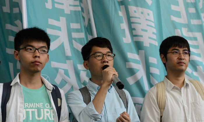 Pro-democracy political activists and members of the Demosisto party (L to R) Joshua Wong, Nathan Law and Alex Chow, speak as they arrive at the Eastern Court in Hong Kong on July 21, 2016. The three were to face a court verdict over charges related to a protest leading up to pro-democracy rallies in 2014. (ANTHONY WALLACE/AFP/Getty Images)