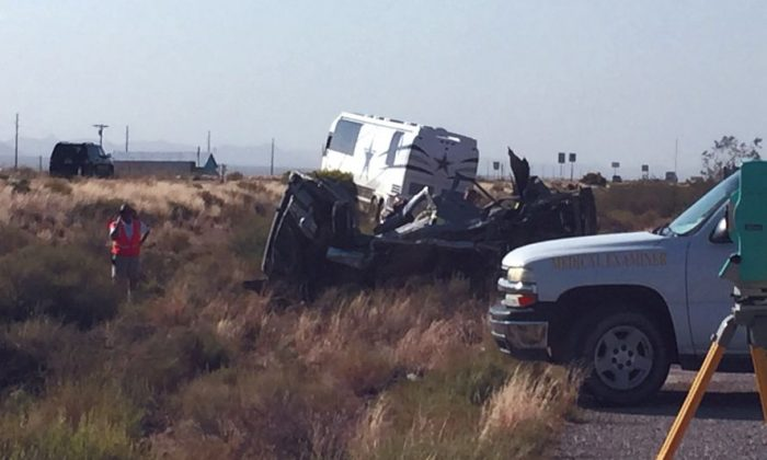 The scene of a bus crash is surveyed Sunday, July 24, 2016, on a highway in northwestern Arizona, about 30 miles north of Kingman. A Dallas Cowboys bus collided with another vehicle and authorities say at least one person was killed. Team spokesman Rich Dalrymple confirmed a Cowboys bus was one of two vehicles involved in the crash Sunday on U.S. 93. (Cody Davis/Kingman Daily Miner via AP)