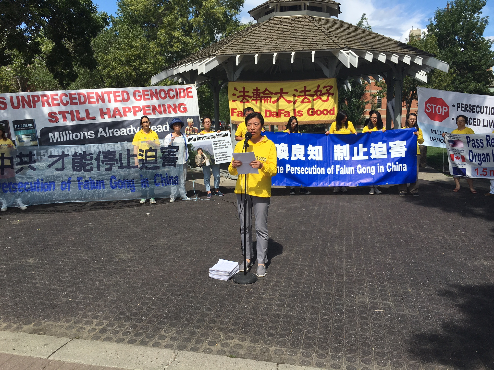 Minnan Liu speaks at a rally in Edmonton on July 23, 2016  to commemorate the 17th anniversary of the persecution of Falun Dafa in China. Liu presented the over 9,000 petitions signed by Edmontonians since last year to bring to justice the former Chinese leader Jiang Zemin who started the persecution on July 20, 1999. Behind her Hongyan Lu holds a sign asking for support to release her mother, Huixia Chen, who is currently detained in China for practicing Falun Dafa.  (Omid Ghoreishi/Epoch Times)