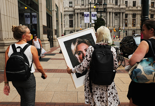 Women walk down a Philadelphia street with a Chuck Close portrait of Hillary Clinton on the first day of the Democratic National Convention (DNC) on July 25, 2016 in Philadelphia, Pennsylvania. (Spencer Platt/Getty Images)