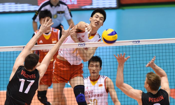 Geng Xin (#11) of China spikes the ball over Graham Vigrass (#17) and John Perrin (#2) of Canada during the men's volleyball world final qualification for the Rio de Janeiro Olympics 2016 in Tokyo on June 5, 2016. (Toru Yamanaka/AFP/Getty Images)