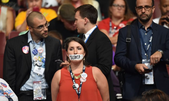 A supporter of former Democratic presidential candidate Bernie Sanders stands in silent protest during Day 1 of the Democratic National Convention at the Wells Fargo Center in Philadelphia, Pennsylvania, July 25, 2016. / AFP / Nicholas Kamm        (Photo credit should read NICHOLAS KAMM/AFP/Getty Images)
