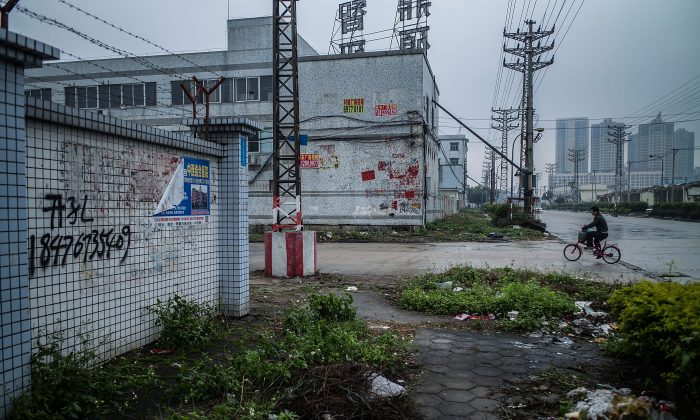 A man rides a bicycle at an abandoned industrial area of Houjie town in Dongguan on Jan. 27, 2016. (Lam Yik Fei/Getty Images)
