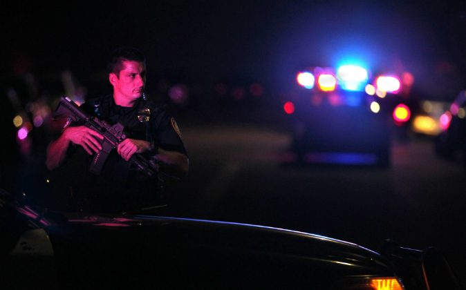 A San Diego Harbor Police officer helps to secure the scene near the corner of 39th Street and Boston Avenue in San Diego near where two San Diego Police officers were shot Thursday night, July 28, 2016. (John Gastaldo/The San Diego Union-Tribune via AP)