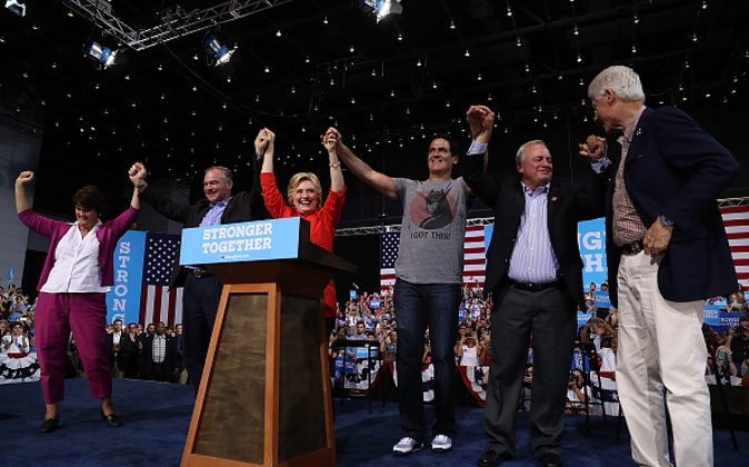 (L-R) Anne Holton, democratic vice presidential nominee U.S. Sen Tim Kaine (D-VA), democratic presidential nominee former Secretary of State Hillary Clinton, Mark Cuban, U.S. Rep. Mike Doyle (D-PA) and former U.S. president Bill Clinton raise arms during a campaign rally  at the David L. Lawrence Convention Center on July 30, 2016 in Pittsburgh, Pennsylvania. (Photo by Justin Sullivan/Getty Images)