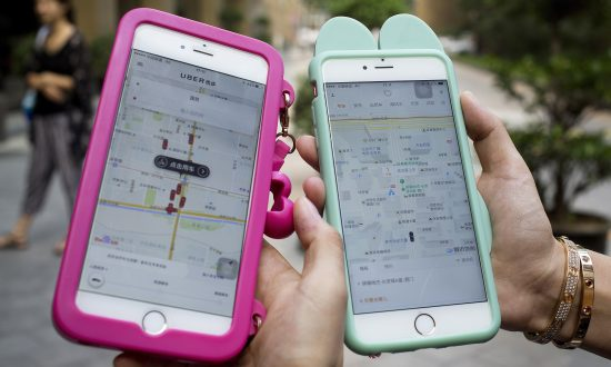 Smartphones show the ride-hailing apps Uber Technology Ltd., left, and Didi Chuxing at a residential compound in Beijing, on  Aug. 1, 2016. (AP Photo/Andy Wong)