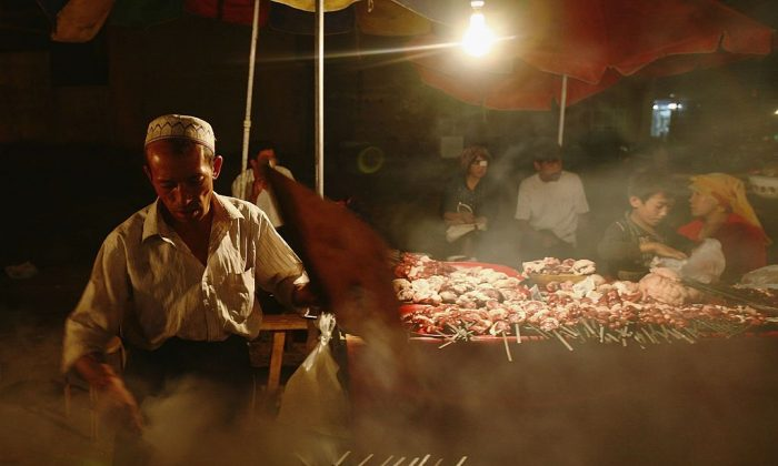 A vendor makes shashlik (kebab) at a booth in Kashi of Xinjiang Uygur Autonomous Region,  on Sept. 20, 2006 (China Photos/Getty Images)