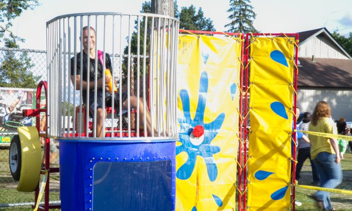 Middletown Police Officer Nathanael DeYoung sits in the dunk tank during Middletown's National Night Out Against Crime in Fancher-Davidge Park on Aug. 2, 2016. (Holly Kellum/Epoch Times)