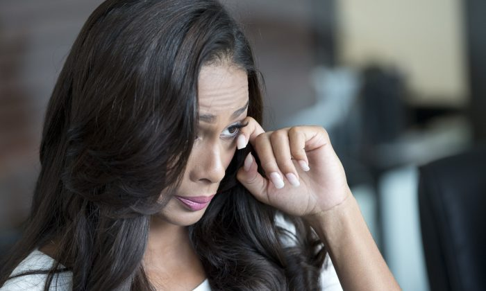 Genesis Davila, Miss Florida USA 2017, who's crown was recently taken away, wipes her eye as she speaks during a news conference in Miami, on Aug. 1, 2016. The Miami Herald reports that attorneys for 24-year-old Davila filed the suit against the pageant Monday, asking a Miami-Dade circuit judge to issue an emergency injunction restoring her title. The suit also seeks $15 million for defamation. (AP Photo/Wilfredo Lee)