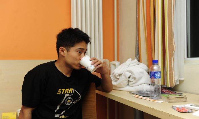 Zhang Shangwu has a drink after an interview at a hotel room in Beijing on July 18, 2011. The champion gymnast forced to turn to begging after injury ended his career prematurely due to an injury. He became a media sensation in China after a fan recognized him eking out a living on the streets of Beijing. Zhang's case throws the spotlight on the plight of top athletes in China, who are taken from their homes as young as five only then to be abandoned and forgotten when they are no longer able to compete. (STR/AFP/Getty Images)