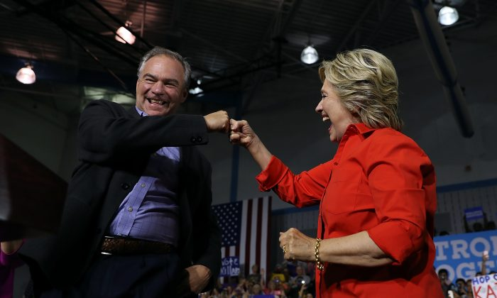 Democratic presidential nominee former Secretary of State Hillary Clinton and democratic vice presidential nominee U.S. Sen Tim Kaine (D-VA) fist bump during a campaign rally at East High School on July 30, 2016 in Youngstown, Pennsylvania. (Justin Sullivan/Getty Images)