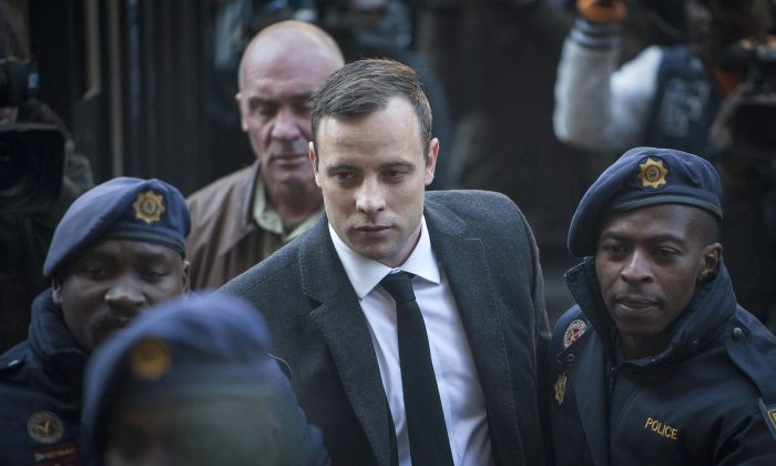 FILE - Oscar Pistorius, center, arrives at the High Court in Pretoria, South Africa, for a sentencing hearing for the murder of his girlfriend Reeva Steenkamp. (AP Photo/Shiraaz Mohamed, File)