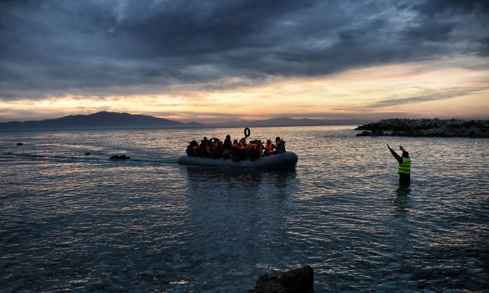 Refugees and migrants massed onto an inflatable boat reach Mytilene, northern island of Lesbos, after crossing the Aegean sea from Turkey on Feb. 17, 2016. (Aris Messinis/AFP/Getty Images)