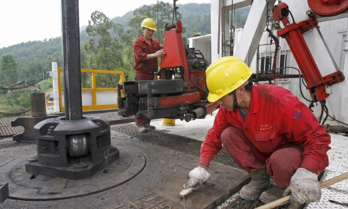 In a file photo, employees work on a drill well at a Sinopec exploration site in the Longgang gas field in Lishan, Sichuan Province. (Liu Jin/AFP/Getty Images)