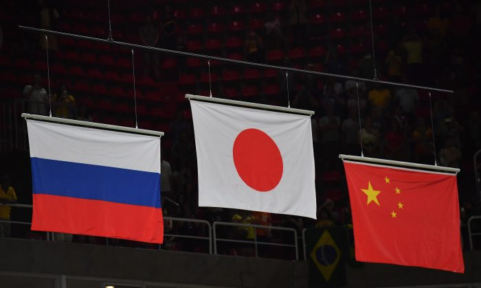 From left to right: Russian, Japanese and Chinese flags displayed at the Olympic arena, after the men's team final of the Artistic Gymnastics during the Rio 2016 Olympic Games on August 8, 2016. (BENSTANSALL/AFP/GettyImages)