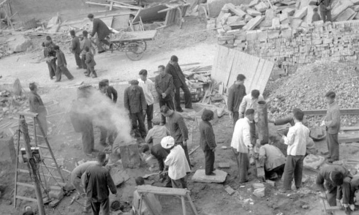 "Employees of the Shin Chiao Hotel in Beijing build in the hotel courtyard (background) in October 1958 a small and rudimentary smelting steel furnace during the period of the ""Great Leap Forward. (JACQUET-FRANCILLON/AFP/Getty Images)"