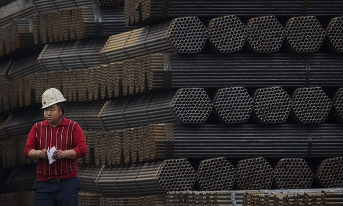 A Chinese steel worker walks past steel rods at a plant in Tangshan, China's Hebei Province, on April 6, 2016. (Kevin Frayer/Getty Images)