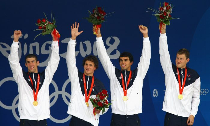 L-R: Michael Phelps, Ryan Lochte, Ricky Berens, and Peter Vanderkaay with their gold medals for the 4x200m freestyle relay at the 2008 Beijing Olympic Games on Aug. 13, 2008. (Paul Gilham/Getty Images)