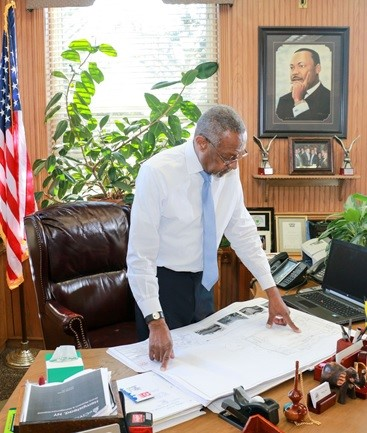 Mayor Hall reviews blueprints for projects included in the village's downtown revitalization project in his office at City Hall in the village of Hempstead, N.Y. (Courtesy Office of Mayor Wayne J. Hall)