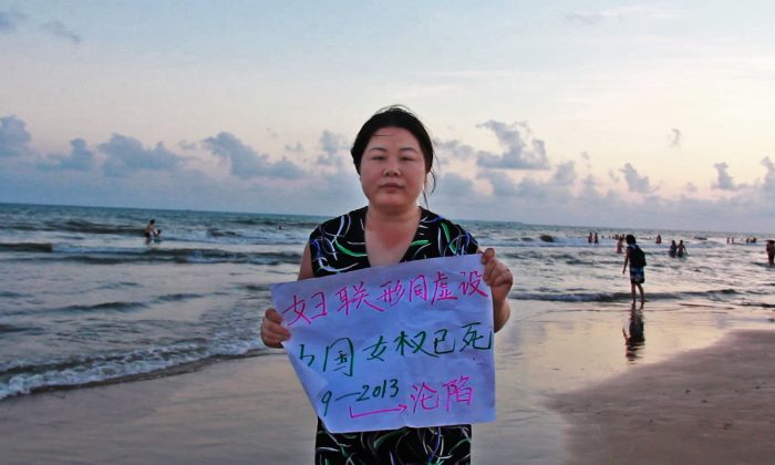 """Ye Haiyan holds a protest sign in the film """"Hooligan Sparrow,"""" which is also her nickname as a women's rights activist. (Courtesy Hooligan Sparrow)"""