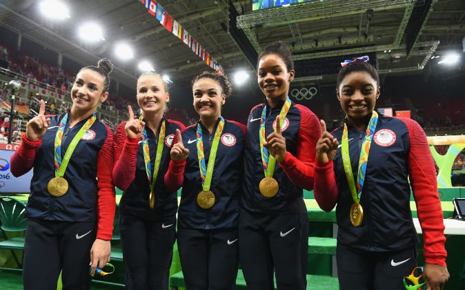 (L to R) Gold medalists Alexandra Raisman, Madison Kocian, Lauren Hernandez, Gabrielle Douglas and Simone Biles of the United States pose for photographs with their medals after the medal ceremony for the Artistic Gymnastics Women's Team on Day 4 of the Rio 2016 Olympic Games at the Rio Olympic Arena on August 9, 2016 in Rio de Janeiro, Brazil. (Laurence Griffiths/Getty Images)