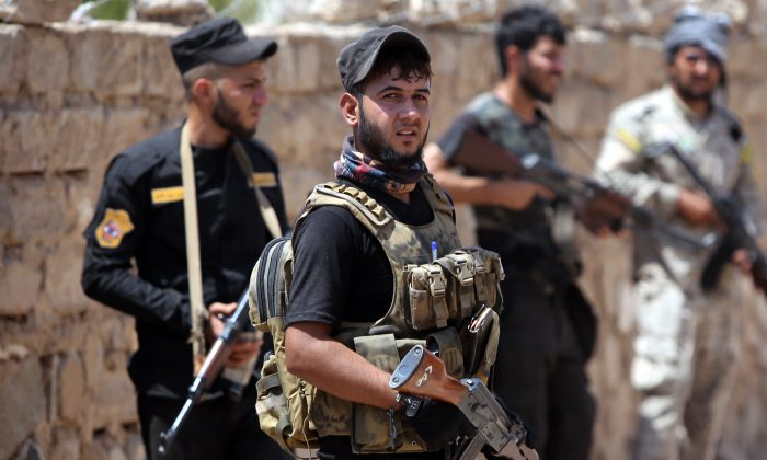 Iraqi fighters from the Shiite popular mobilisation unit hold their weapons in the outskirts of Baiji refinery north of Tikrit on May 25, 2015. (AHMAD AL-RUBAYE/AFP/Getty Images)        (Photo credit should read AHMAD AL-RUBAYE/AFP/Getty Images)