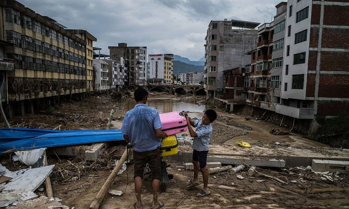 People leave home in the damaged village at Bandong Town on July 12, 2016 in Fuijan, China. (Lam Yik Fei/Getty Images)