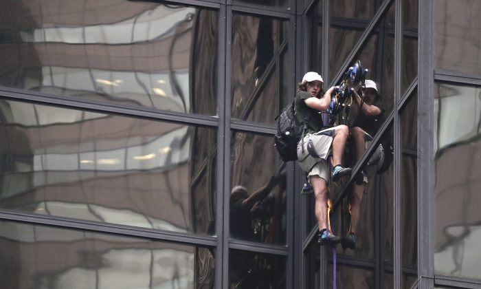 A man scales the all-glass facade of Trump Tower using suction cups Wednesday, Aug. 10, 2016, in New York. A police spokeswoman says officers responded to Donald Trump's namesake skyscraper on Fifth Avenue in Manhattan. The 58-story building is headquarters to the Republican presidential nominee's campaign. He also lives there. (AP Photo/Julie Jacobson)