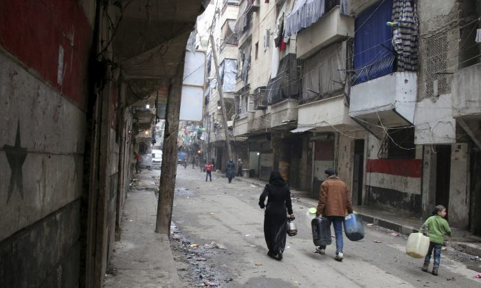 In this Feb. 11, 2016, file photo, civilians walk with containers for fuel and water in Aleppo, Syria. Syrian rescue worker says three civilians, a mother and two children, died in a suspected chlorine gas attack on an opposition-held district in the city of Aleppo. The report, which was posted online on Thursday, Aug. 11, could not be independently verified and it was not clear how it was determined that chlorine gas was released. (Alexander Kots/Komsomolskaya Pravda via AP, File)