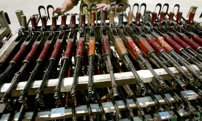 An Israeli army officer stands behind rows of captured AK-47 assault rifles on display at an army base April 10, 2002 near the central Israeli town of Ramle. (David Silverman/Getty Images)