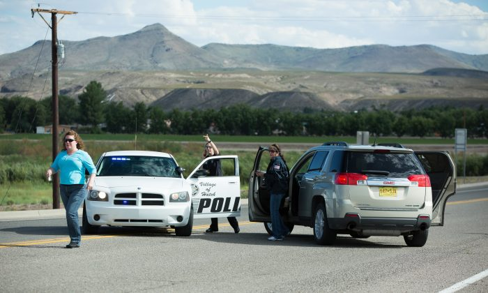 Police officers and state employees prevent drivers from entering Hatch, N.M., after a shooting on Aug. 12, 2016. Dona Ana County authorities say a Hatch police officer has died after being shot during a traffic stop on Friday. (Anayssa Vasquez/The Las Cruces Sun-News via AP)