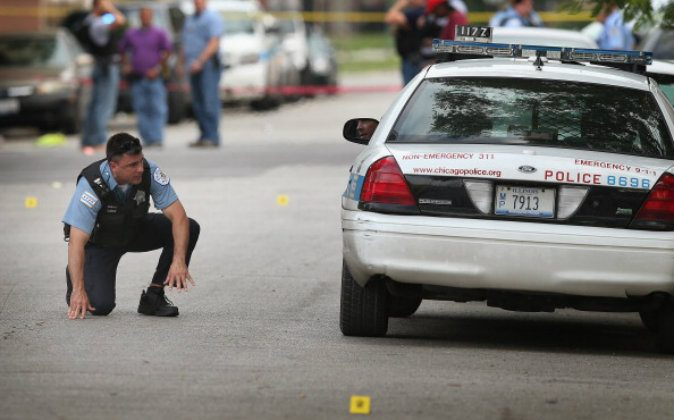 Police investigate a crime scene where seven people were shot on July 6, 2013 in Chicago, Illinois. (Scott Olson/Getty Images)