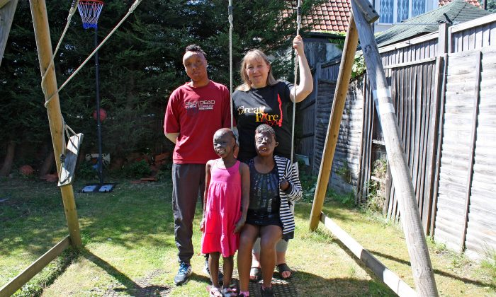 Bronwen Jones with her adopted son, Sizwe, 15, adpoted daughter, Dorah, 22 and her foster-daughter, 8-year-old Perlucia at her home in Pinner, London on August 12 2016. (Jane Gray/Epoch Times)