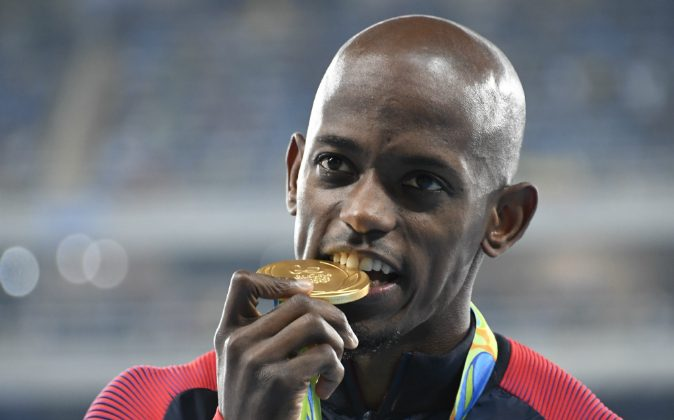 USA's Jeff Henderson bites the gold medal during the podium ceremony for the Men's Long Jump at the athletics event at the Rio 2016 Olympic Games at the Olympic Stadium in Rio de Janeiro on August 14, 2016. (DAMIEN MEYER/AFP/Getty Images)