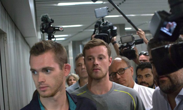 Journalists surround American Olympic swimmers Gunnar Bentz, left, and Jack Conger, center, as they leave the police station at Rio International airport Aug. 18, 2016. (AP Photo/Mauro Pimentel)