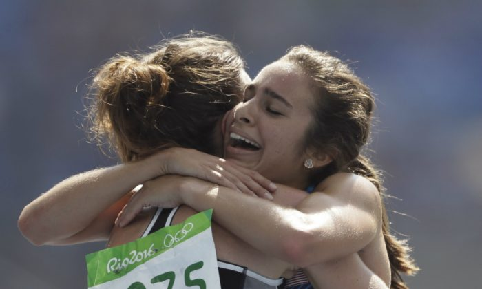 New Zealand's Nikki Hamblin, left, and United States' Abbey D'Agostino after competing in a women's 5000-meter heat during the athletics competitions of the 2016 Summer Olympics at the Olympic stadium in Rio de Janeiro, Brazil on Aug. 16, 2016. (AP Photo/David J. Phillip)