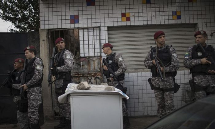 Brazil's national security force officers move inside the Vila do Joao, part of the Mare complex of slums, during a police operation in search for criminals during the 2016 Summer Olympics in Rio de Janeiro, Brazil, Thursday, Aug. 11, 2016. A police officer has died after being shot in the head when he and two others working security at the Rio Olympics got lost near a slum and encountered gunfire. (AP Photo/Felipe Dana)