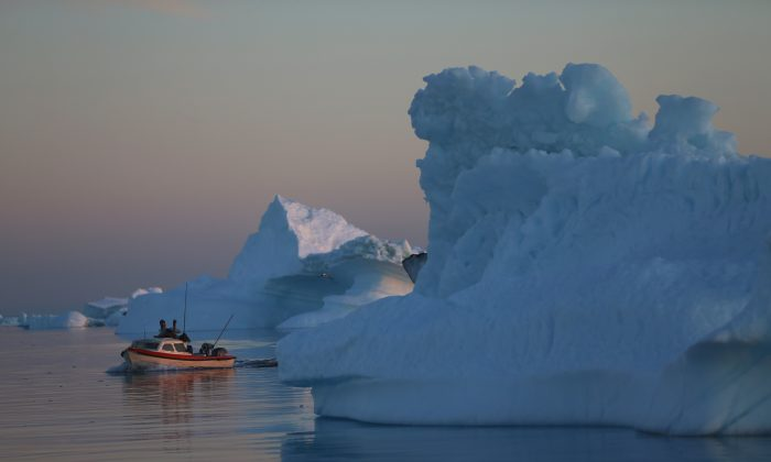 A fishing boat navigates past icebergs that broke off from the Jakobshavn Glacier in Ilulissat, Greenland on July 23, 2013. (Joe Raedle/Getty Images)