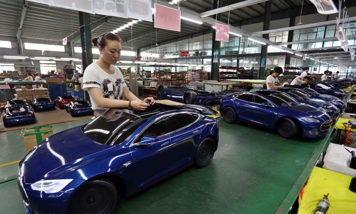 Chinese worker assembles toy cars at a factory in Jinjiang, Fujian Province on July 1, 2016. (STR/AFP/Getty Images)